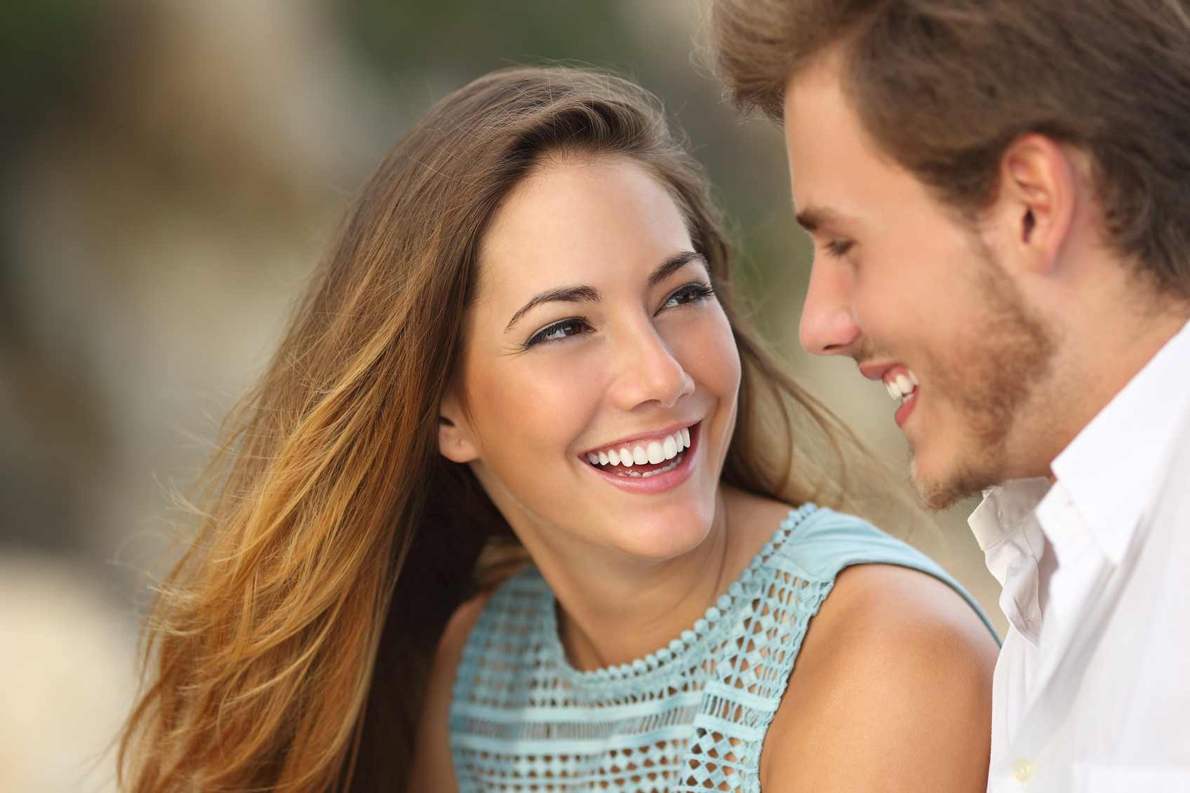 Funny couple laughing with a white perfect smile and looking each other outdoors with unfocused background